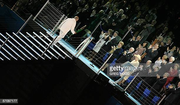 Former Australian Olympic star John Landy climbs the stairs with the Queen's Baton to present it to Queen Elizabeth II during the opening ceremony...