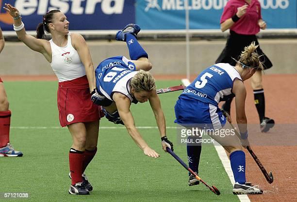 Forward Rhonda Simpson of Scotland dives between England midfielder Jennie Bimson and teammate Catriona Semple during their women's field hockey...