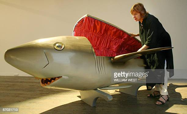 Gallery worker Mary Lou Jelbant inspects a coffin carved in the shape of a shark by the Paa Joe Carpentry workshop in Ghana and commissioned for...