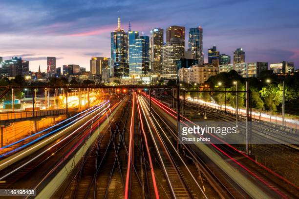 melbourne cbd cityscape towards flinders train station with metro train coming in railway station at night in melbourne, victoria, australia. - melbourne australia foto e immagini stock