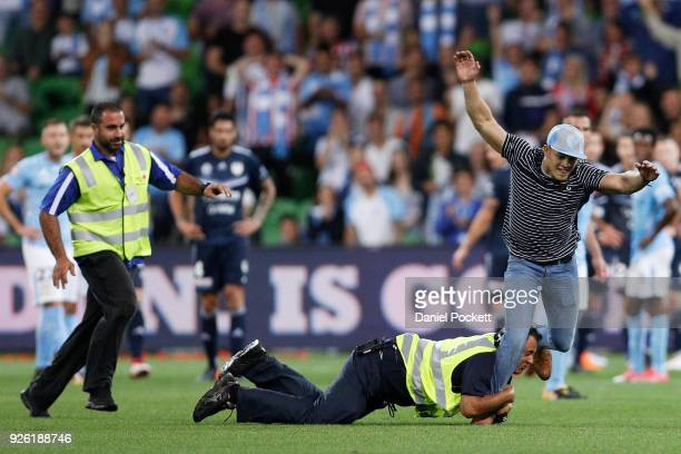 Melbourne City fan invades the pitch snd is chased by security during the round 22 ALeague match between Melbourne City FC and Melbourne Victory at...