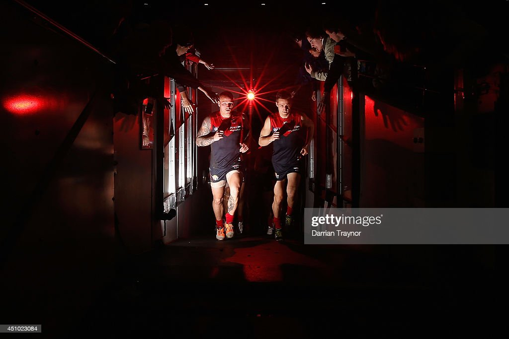 Melbourne co-captains Nathan Jones and Jack Grimes lead the team out after the half time break during the round 14 AFL match between the Melbourne Demons and the North Melbourne Kangaroos at Melbourne Cricket Ground on June 22, 2014 in Melbourne, Australia.
