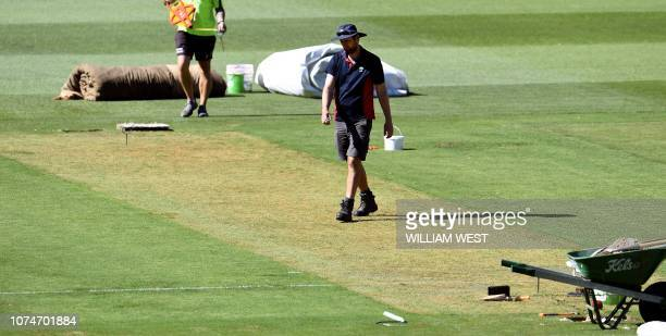 Melbourne Cricket Ground curator Matt Page walks over the wicket during Australia's cricket training in Melbourne on December 24 ahead of the third...