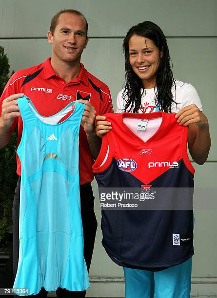 Melbourne Demon AFL player David Neitz and Ana Ivanovic of Serbia hold up each others sporting attire offcourt on day six of the Australian Open 2008...
