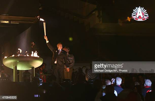 Melbourne Football Club legend Ron Barassi holds up the torch after lighting the Anzac Cauldron during the round four AFL match between the Richmond...