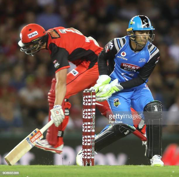 Melbourne Renegades Cameron White narrowly makes his ground as Strikers Alex Carey takes the ball during the Big Bash League match between the...