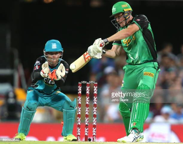 Melbourne Stars player James Faulkner hits the ball as Brisbane keeper Jimmy Peirson looks on during the Big Bash League match between the Brisbane...