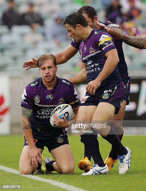 Melbourne Storm players celebrate a try by Cameron Munster during the round six NRL match between the Canberra Raiders and the Melbourne Storm at GIO...