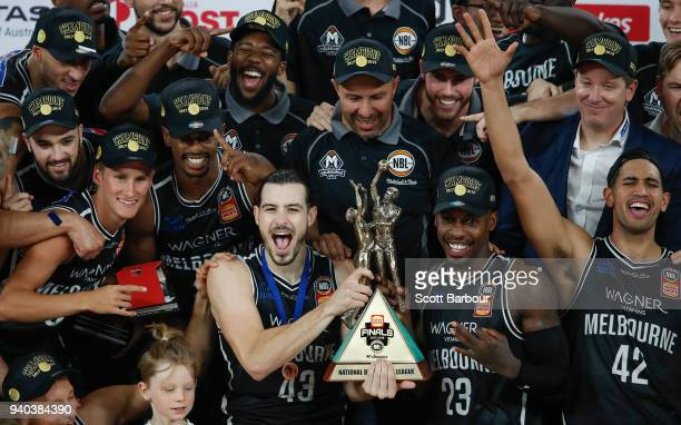Melbourne United captain Chris Goulding, Casey Prather of Melbourne United and their teammates celebrate as they are presented with the trophy after...