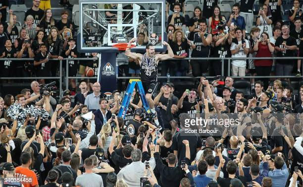 Melbourne United captain Chris Goulding celebrates with fans as he cuts down the net after winning game five of the NBL Grand Final series between...