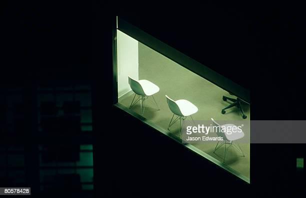 Three empty white plastic chairs line an  office window at night.