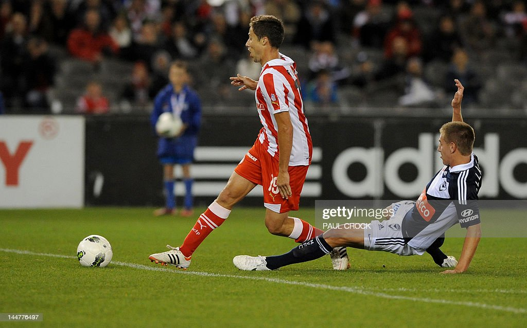 Melbourne Victory player Samuel Gallagher (R) tries to tackle Olympiakos player David Fuster (L) during their football match in Melboune on May 19, 2012. IMAGE STRICTLY RESTRICTED TO EDITORIAL USE - STRICTLY NO COMMERCIAL USE AFP PHOTO/Paul CROCK
