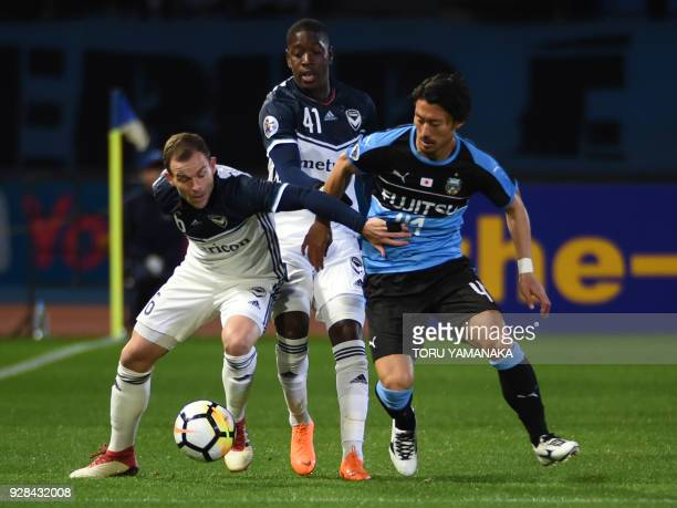 Melbourne Victory's midfielder Leigh Broxham and teammate forward Leroy Marten George tussle for the ball with Kawasaki Frontale's midfielder Akihiro...