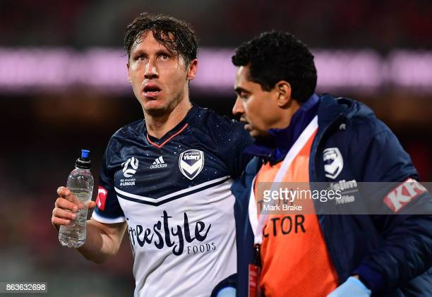 Melbourne's Mark Milligan goes off after being sandwiched between Adelaides Vince Lia and Melbourne's Leigh Broxham defending a goal during the round...