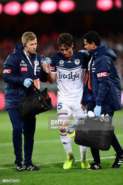 Melbourne's Mark Milligan is sandwiched between Adelaides Vince Lia and Melbourne's Leigh Broxham defending a goal and leaves the field during the...