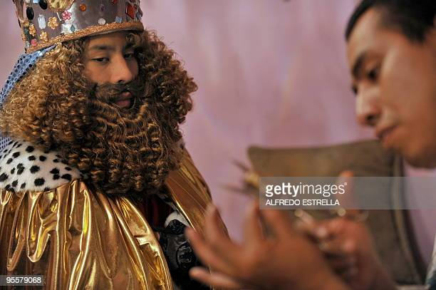 'Melchoir' waits for his false eyelashes during the preparation of the Three Wise Men in Mexico City's Guerrero neighbourhood before a walk around...