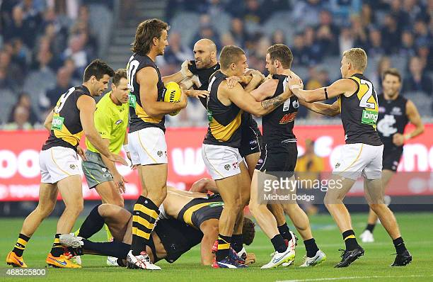 A melee breaks out during the round one AFL match between the Carlton Blues and the Richmond Tigers at Melbourne Cricket Ground on April 2 2015 in...