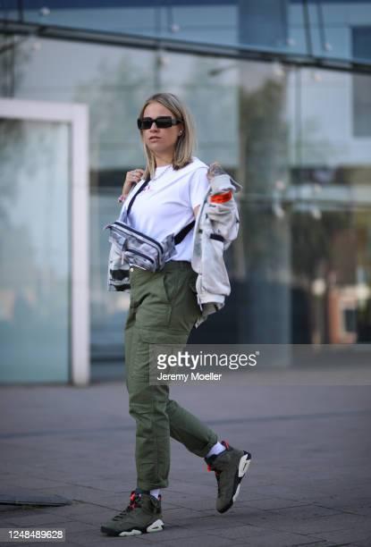 Melina Sophie wearing Heron Preston belt bag and jacket, white shirt and Nike sneaker on June 06, 2020 in Hamburg, Germany.