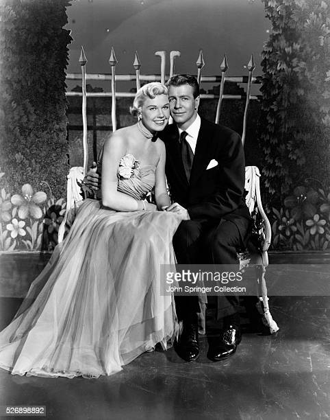 Melinda Howard sits on a cozy bench with Tom Farnham in a publicity still for the 1051 film Lullaby of Broadway
