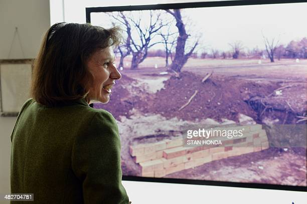 Melinda Hunt of the Hart Island Project speaks in front of a large transparency of a photograph by Joel Sternfeld of infant coffins on Hart Island...