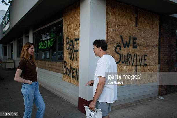 """Melinda Nagle and Ken Siegel talk on the street in front of a sign on Ken's store reading' """"Bent not Broken and We survive""""' in downtown after the..."""