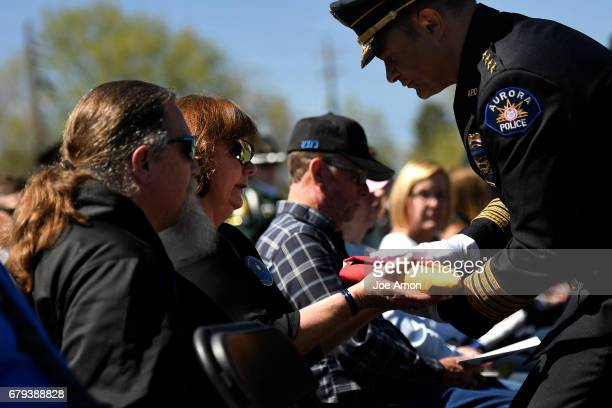 Melissa Carrigan and her husband John parents of fallen Park County Sheriff's Deputy Cpl Nathaniel Carrigan receive a Colorado Flag from Aurora...
