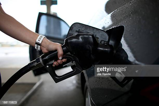 Melissa Cassidy pumps gas into her car from a pump with a sign indicating the gas is containing up to 10 % ethanol at Victory gas station on November...