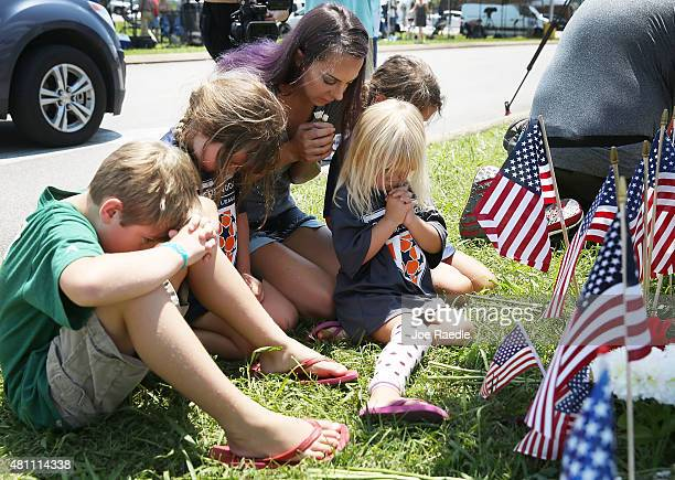 Melissa Gallagher prays with her children as they pay their respects to those killed while visiting a memorial placed in front of the Armed Forces...