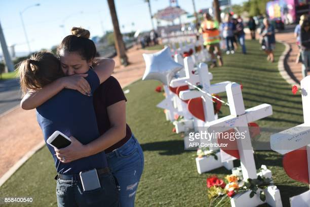 TOPSHOT Melissa Gerber and Sandra Serralde comfort each other beside 58 white crosses for the victims of Sunday night's mass shooting on the south...