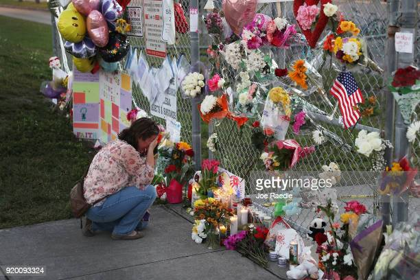 Melissa Goldsmith is over come with emotion as she visits a makeshift memorial setup in front of Marjory Stoneman Douglas High School on February 18...