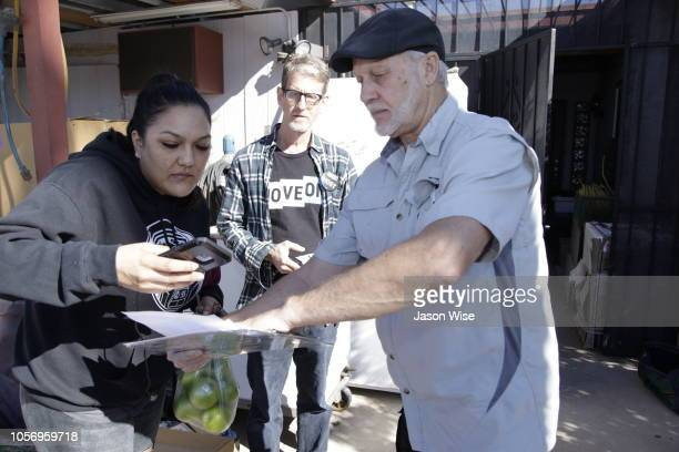 Melissa Leon speaks with David Nevins and George Rowe of MoveOn while they canvass for Ann Kirkpatrick on November 3 2018 in Tucson Arizona