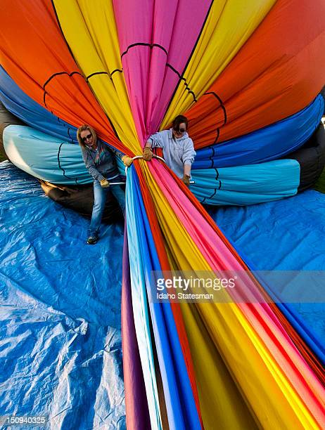 Melissa Roll left and Jennifer Pengelly of Boise pushes the air out of a hot air balloon before packing it away after the first day of the annual...