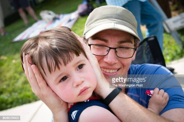 Melissa Scopilliti of College Park Maryland hold's the ears of her daughter Evelyn Poling as fire engines and ambulances with sirens pass Takoma...