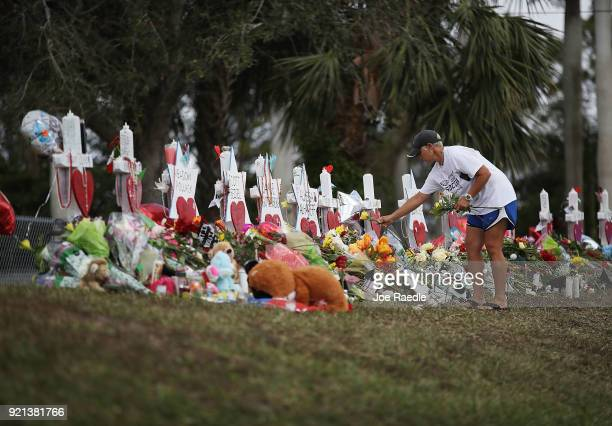 Melissa Shev visits a makeshift memorial setup in front of Marjory Stoneman Douglas High School in memory of the 17 people that were killed on...
