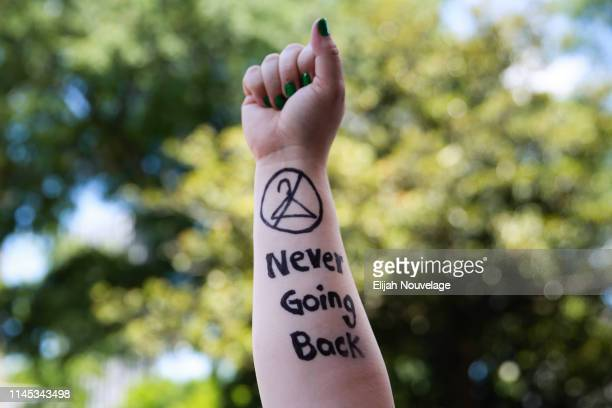 Melissa Simpson holds up her arm with Never Going Back written on it during a protest against recently passed abortion ban bills at the Georgia State...