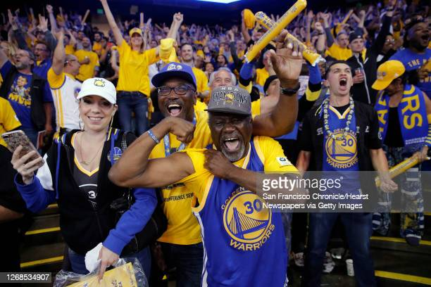 Melissa Valdez, Don Smith and Ahmad Rashadd celebrat the victory as the Golden State Warriors went on beat on the Cleveland Cavaliers 129-120 in game...