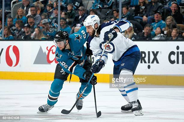 Melker Karlsson of the San Jose Sharks and Chris Thorburn of the Winnipeg Jets nudge each other for position during a NHL game at SAP Center at San...