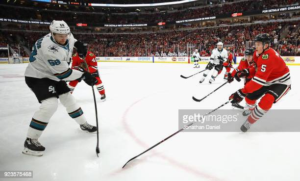 Melker Karlsson of the San Jose Sharks gets off a shot at Connor Murphy of the Chicago Blackhawks at the United Center on February 23 2018 in Chicago...