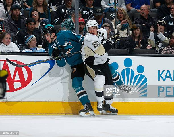 Melker Karlsson of the San Jose Sharks takes a hit from Sidney Crosby of the Pittsburgh Penguins at the SAP Center on March 9 2015 in San Jose...
