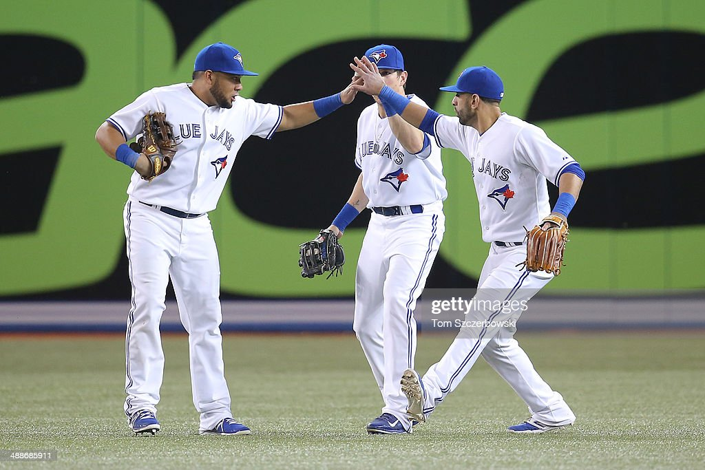 Melky Cabrera #53, Colby Rasmus #28 and Jose Bautista #19 of the Toronto Blue Jays celebrate their victory during MLB game action against the Philadelphia Phillies on May 7, 2014 at Rogers Centre in Toronto, Ontario, Canada.