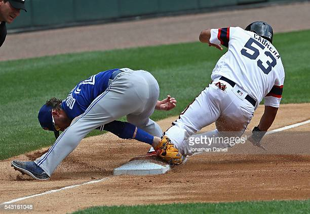 Melky Cabrera of the Chicago White Sox appears to safely slide into third base as Josh Donaldson of the Toronto Blue Jays attempts to make the tag...