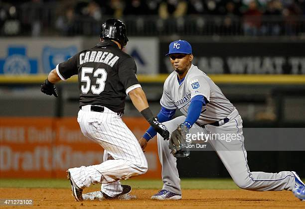 Melky Cabrera of the Chicago White Sox slides safely into second base for a double as Alcides Escobar of the Kansas City Royals takes the throw the...