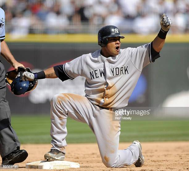 Melky Cabrera of the New York Yankees reacts after sliding safely into third base with a triple, thus hitting for the cycle, in the ninth inning...