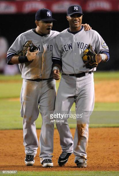 Melky Cabrera of the New York Yankees talks with teammate Robinson Cano in Game Five of the ALCS against the Los Angeles Angels of Anaheim during the...