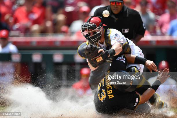 Melky Cabrera of the Pittsburgh Pirates scores a run in the fourth inning as he collides with catcher Tucker Barnhart of the Cincinnati Reds at Great...