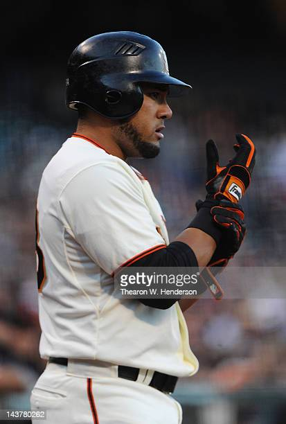 Melky Cabrera of the San Francisco Giants looks on while tightening up his franklin batting glove in the ondeck circle against the Miami Marlins at...