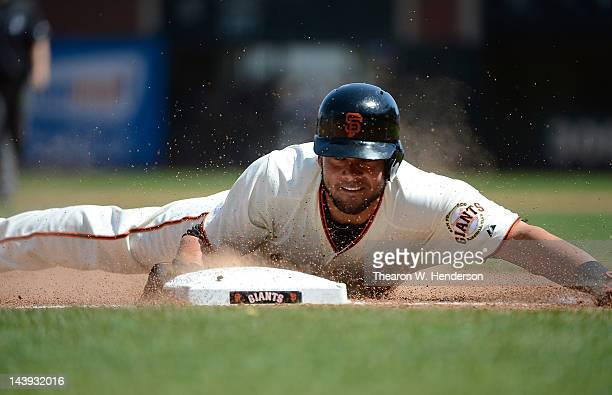 Melky Cabrera of the San Francisco Giants slides in head first to third base with a triples in the six inning against the Milwaukee Brewers at ATT...