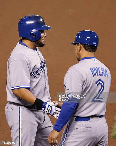 Melky Cabrera of the Toronto Blue Jays is congratulated by third base coach Luis Rivera after hitting a triple against the Baltimore Orioles in the...