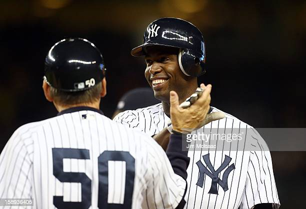 Melky Mesa of the New York Yankees celebrates his first career hit an eighth inning RBI single against the Boston Red Sox with first base coach Mick...