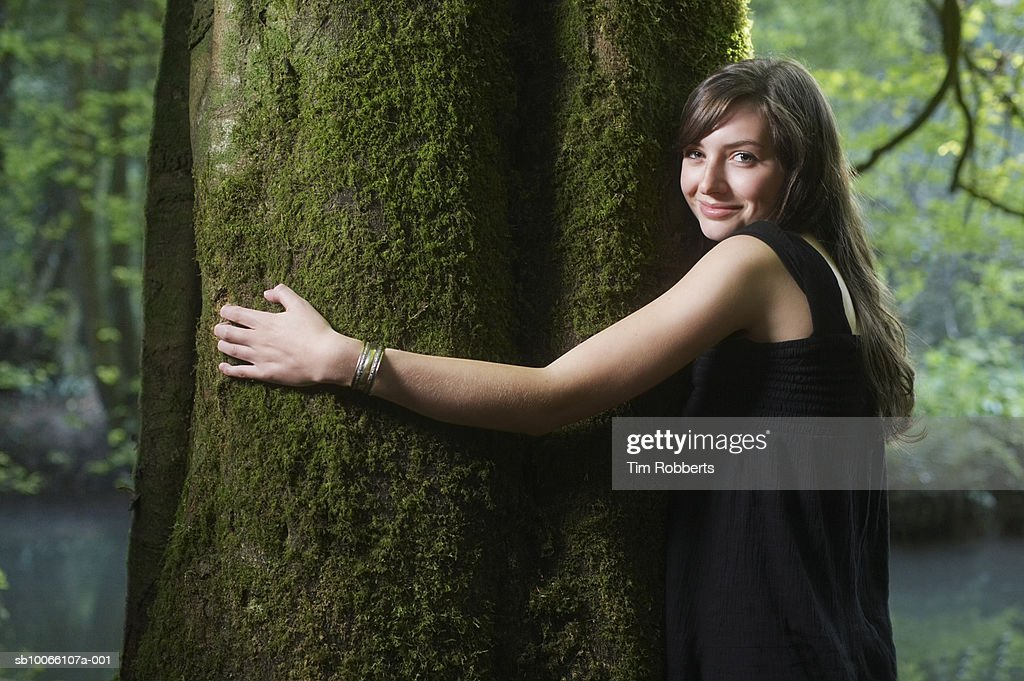 UK, Mells, Somerset, young woman hugging tree in forest, portrait : Stock Photo